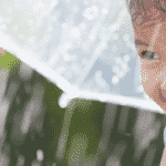 girl with umbrella playing in rain